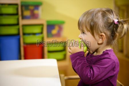 weibliches kind gruenen apfel isst im