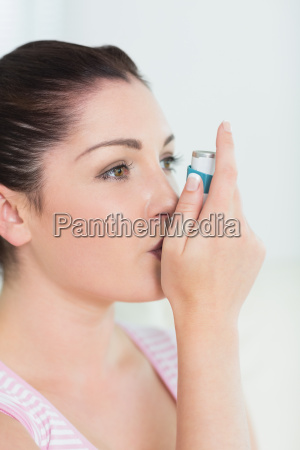 woman with asthma using an asthma