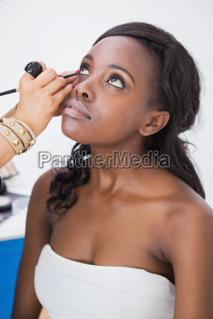 makeup artist applying eyeliner to woman