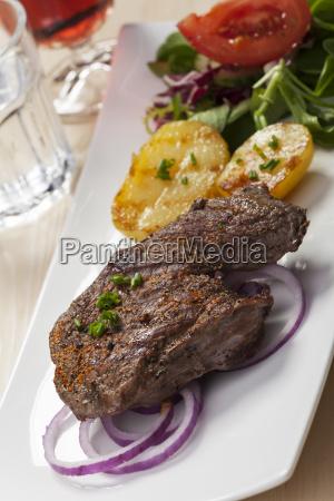 steak with potato halves and salad