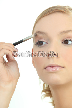young woman applying eyeshadow