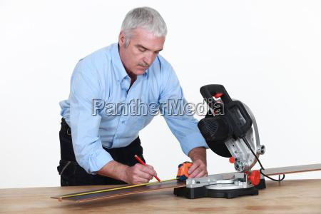 a senior carpenter with a circular