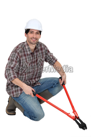 man kneeling with bolt cutters