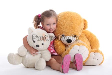 little girl hugging two big teddy