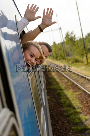 couple waving with heads out train
