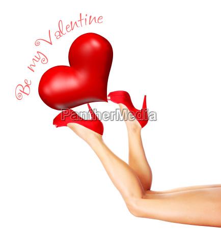 beautiful female legs holding heart