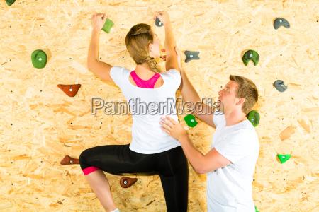 woman and man climbing in climbing