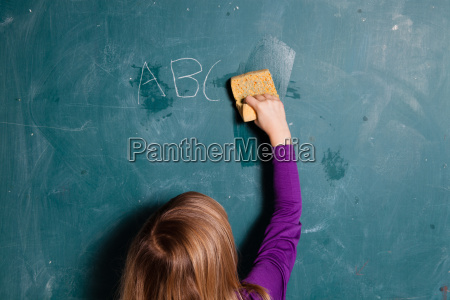 young girl wiping chalkboard with wet