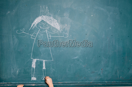 child drawing picture on chalkboard