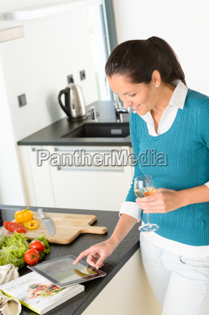 woman searching recipe tablet kitchen vegetables