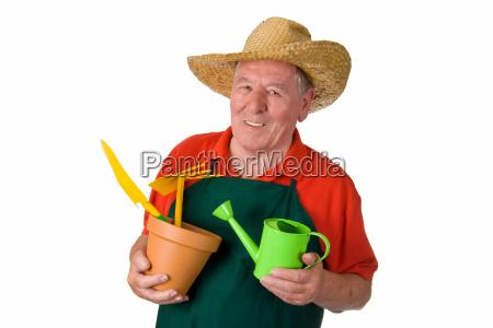 senior gardener holding gardening tools