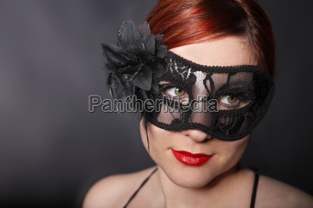young woman with black carnival mask