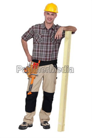 carpenter stood with plank of wood