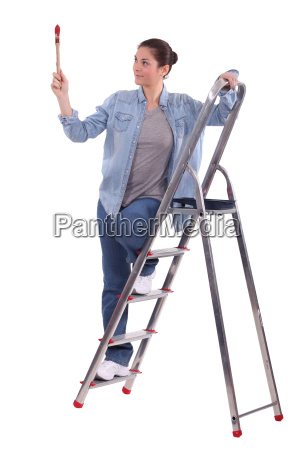 young female painter on ladder with