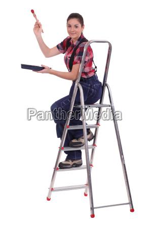 female painter on ladder against white