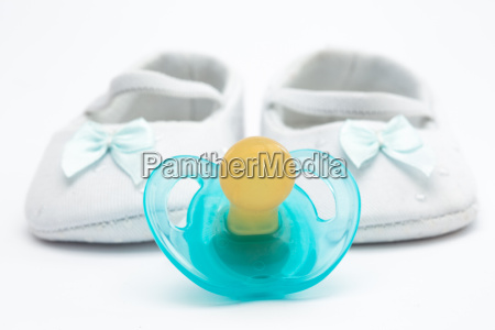 blue soother with baby booties on