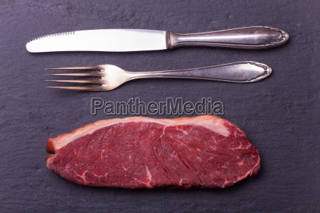 raw steak and cutlery on slate