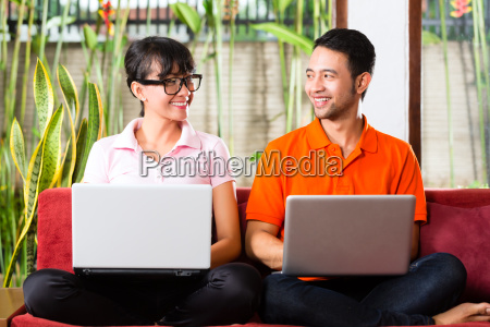 asian couple on the couch with