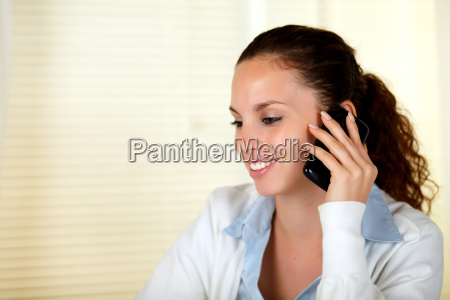 smiling woman speaking on cellphone