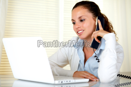 charming young woman reading on laptop