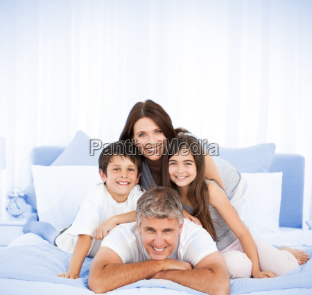 happy family portrait in bed with