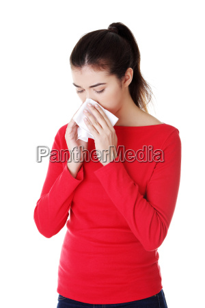 young woman with tissue sneezing