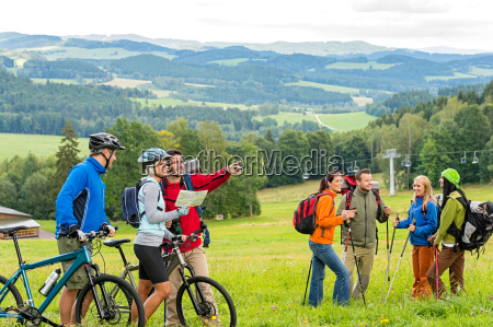 hikers helping cyclists following track nature