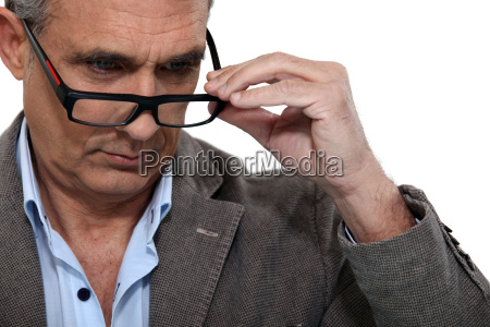 senior putting on his glasses
