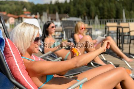 young women lying on deckchair applying