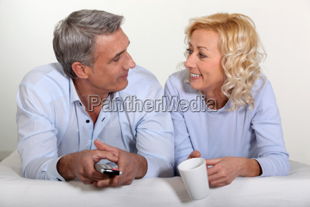couple laying on bed watching television