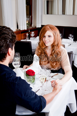 happy young couple celebrating at restaurant
