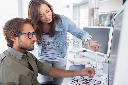 editors choosing photos on computer screen
