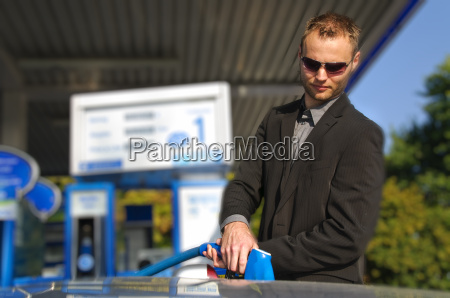 young man with convertible at gas