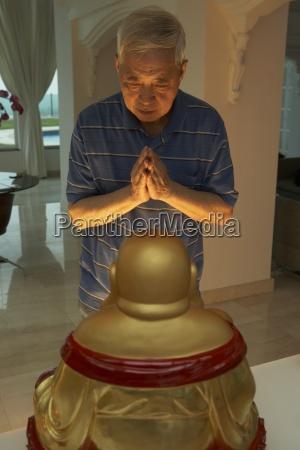 senior chinese man praying to statue