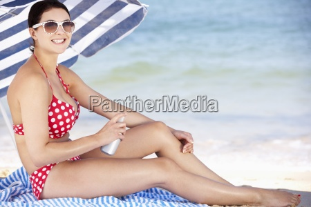 woman sheltering from sun under beach