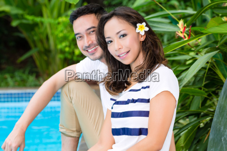 asian couple standing outside the pool