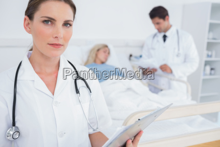 serious doctor holding folder in front