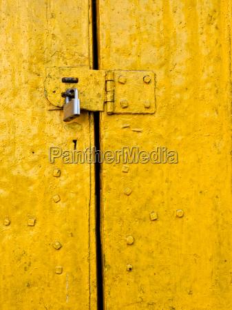 padlock on an old yellow door