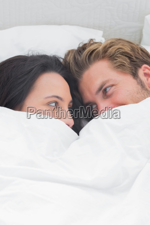 couple under the quilt looking at
