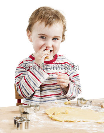happy young child nibbling dough in