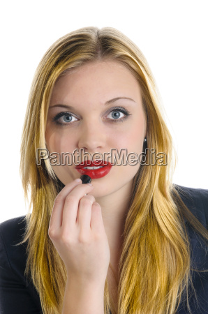 young girl applying red lipstick