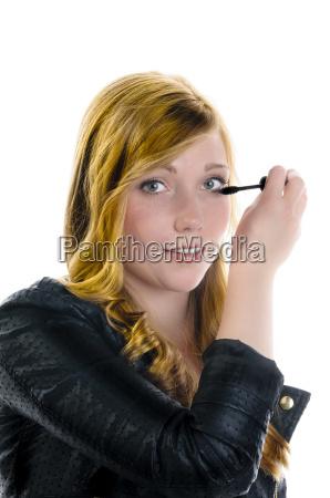 young girl applying mascara