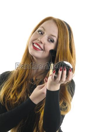 young girl applying rouge