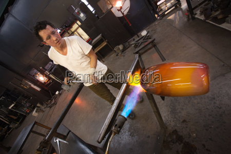 glass worker with vase and blowtorch