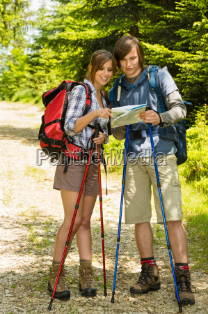 young hikers couple checking the map
