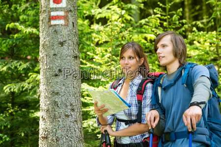 young tourists checking the map and