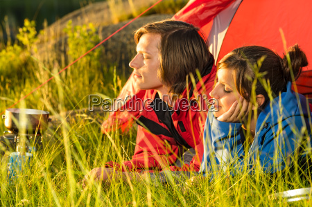 young couple enjoying sunset from tent