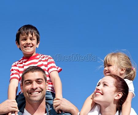 happy parents giving their children piggyback