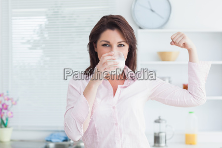 woman drinking milk and flexing muscles