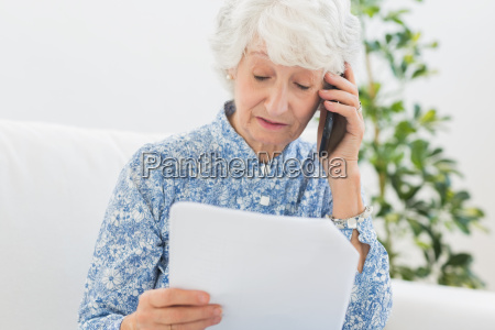 elderly woman reading papers on the